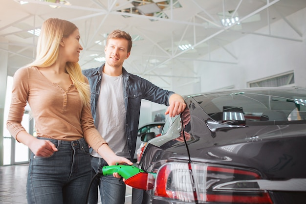 Young smiling family couple buying first electric car in the showroom. close-up of attractive woman charging ecological hybrid car with the power cable supply plugged in while watching at her husband.