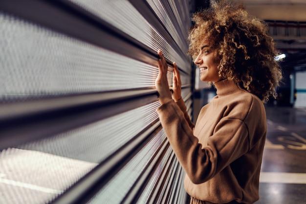 地下駐車場に立っている巻き毛の若い笑顔のファッショナブルな女性。