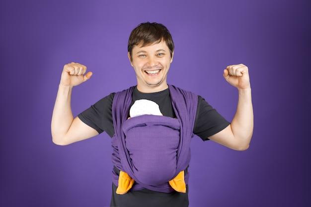 スリングフロントラップで若い笑顔の父と赤ちゃんは幸せな父性フリーハンドベビーウェアを運ぶ