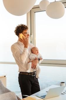 Молодой улыбающийся отец-бизнесмен играет со своим маленьким сыном во время разговора по мобильному телефону дома