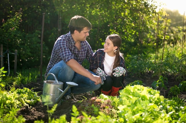 Молодой улыбающийся отец учит дочь садоводству в саду