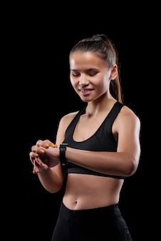 Young smiling female in activewear looking at her wristwatch while going to have break after workout in isolation