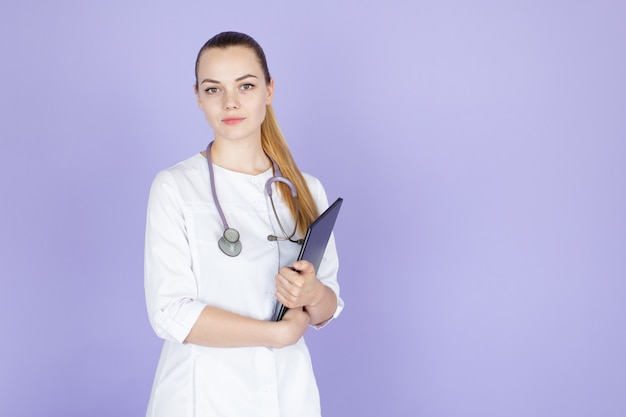 Young smiling female blonde doctor with long hair ponytale with stethoscope on her neck.