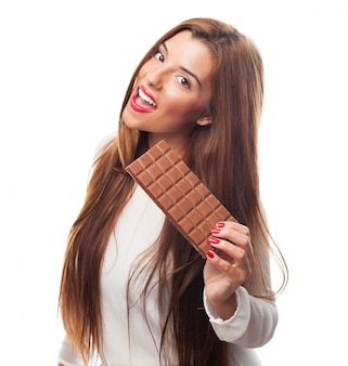 チョコレートのバーを表示する若い笑顔の女性。
