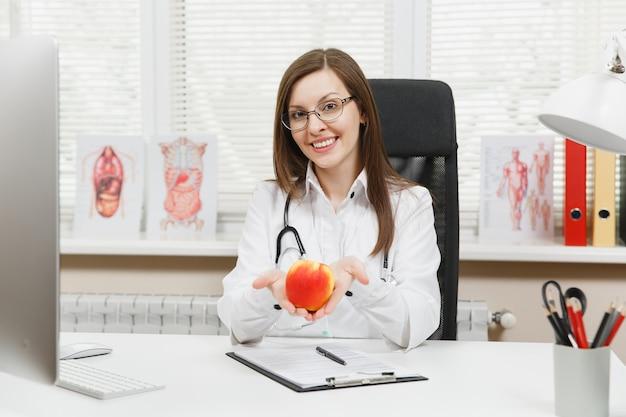 책상에 앉아 웃고 있는 젊은 여성 의사, 병원의 가벼운 사무실에서 의료 문서로 컴퓨터 작업