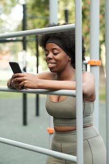 스마트폰으로 스크롤하는 운동복을 입은 젊은 웃는 여성