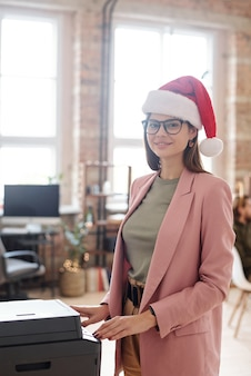 Молодая улыбающаяся женщина в рождественской шапочке и очках смотрит на вас, делая копии документов на ксерокопии в офисе