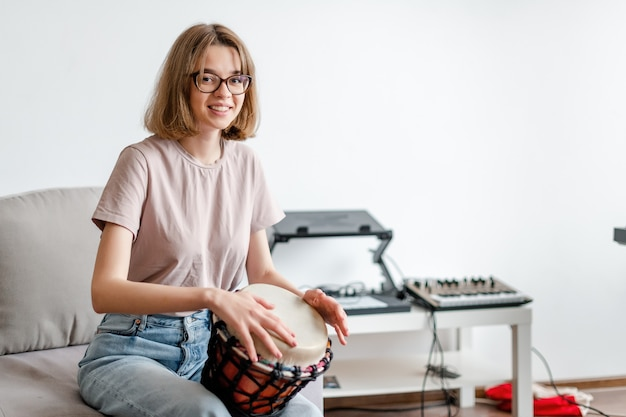 Young smiling female learning how to play djembe at home copyspace