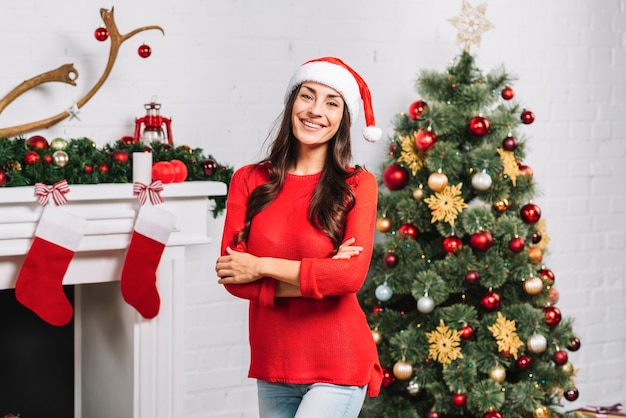 Young smiling female near christmas tree