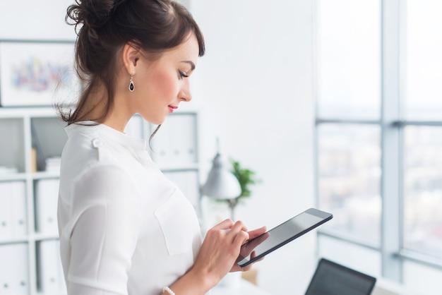 休憩中にタブレットコンピューターを使用してニュース広告メッセージを読んで、彼女の職場で若い笑顔の女性サラリーマン。