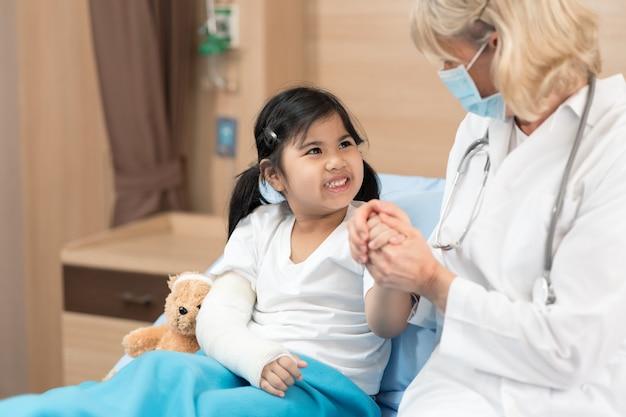 健康医療センターで若い笑顔の女性小児科医とテディベアの子供患者