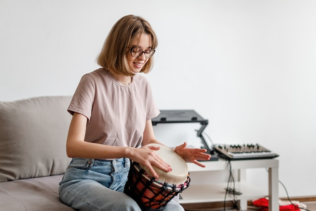 Young smiling female playing djembe drum at home