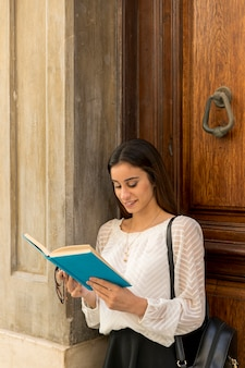 Young smiling female reading near wooden doors
