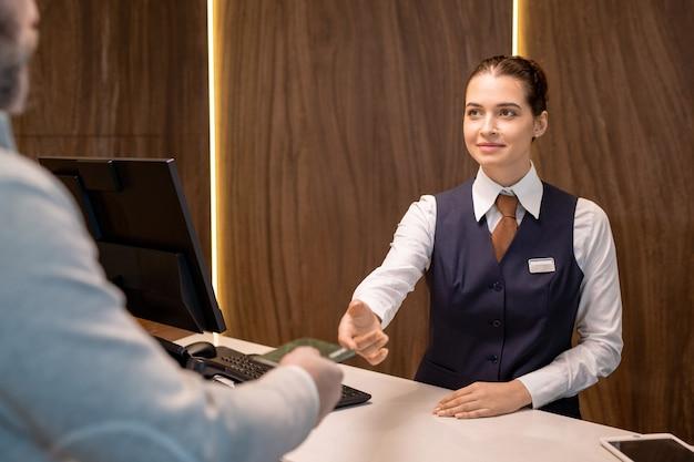 Молодая улыбающаяся женщина-регистратор в униформе, стоящая у прилавка и смотрящая на зрелого бизнесмена, принимая его документы для проверки