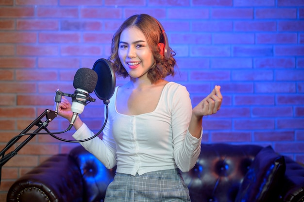 A young smiling female singer wearing headphones with a microphone while recording song in a music studio with colorful lights.