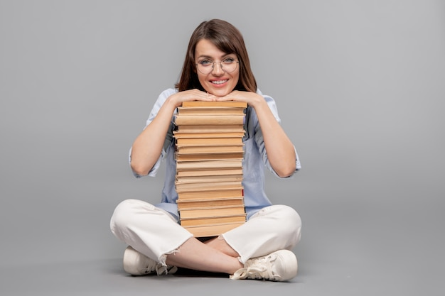 Young smiling female student with her chin over high stack of books to read looking at you in isolation
