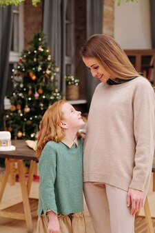 집에서 장식 된 firtree에 대해 카메라 앞에 서있는 동안 그녀의 귀여운 작은 딸과 이야기하는 젊은 웃는 여성