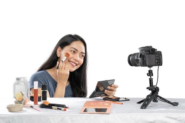 Молодая улыбающаяся женщина-видеоблогер использует кисть с косметическим продуктом на столе перед камерой