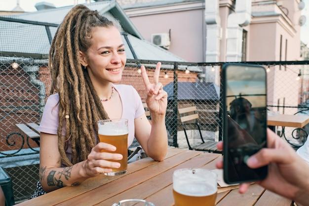 야외 카페 테이블 옆에서 스마트폰 카메라를 위해 포즈를 취하는 향취를 가진 젊은 미소 여성