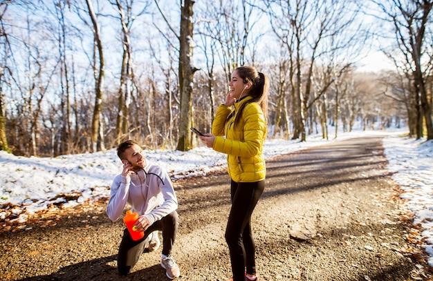 晴れた冬の朝、森をジョギングした後、水と音楽で休憩をとるスポーツウェアの若い笑顔のフィットネスカップル。
