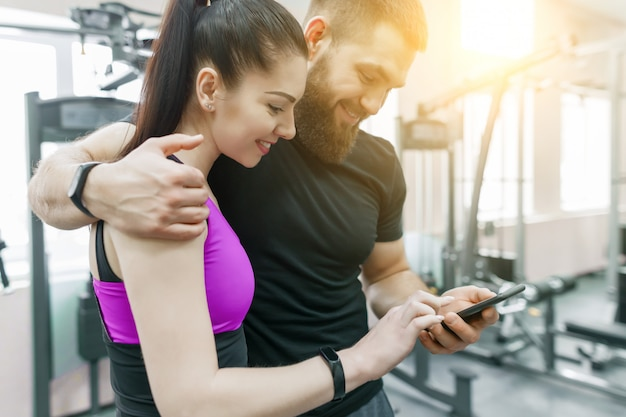 Young smiling fitness couple talking in the gym.