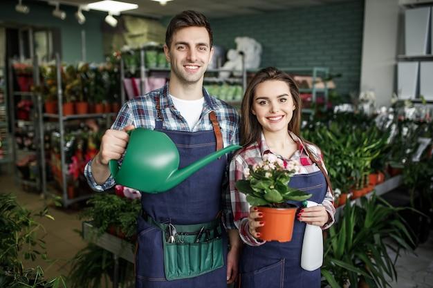 Молодые улыбающиеся флористы, работающие в теплице