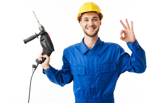 Young smiling foreman in blue uniform and yellow helmet joyfully showing ok gesture lwhile ooking in camera holding drilling machine in hand