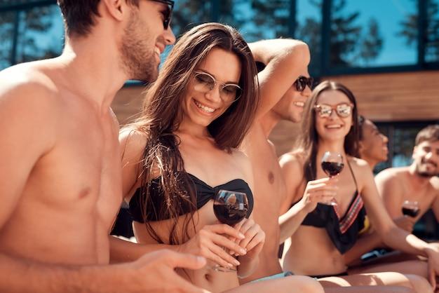 Молодые улыбающиеся друзья пьют вино у бассейна