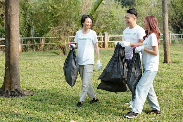 Young smiling friends joking around when picking up garbage on campus or in city park
