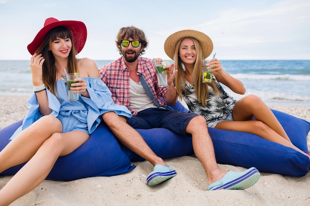 Молодые улыбающиеся друзья в отпуске, сидя в мешках с фасолью на пляжной вечеринке