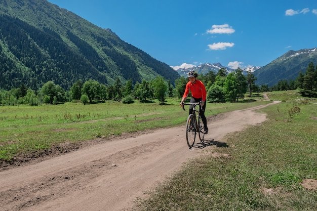 A young smiling girl on a cyclocross bike rides along a winding mountain road against a background of green forest and mountains with glaciers and snow on the tops
