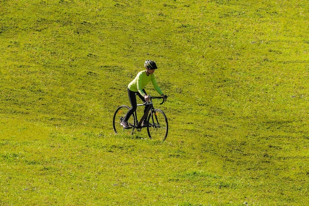 A young smiling girl on a cyclocross bike rides a green bright meadow down the slope