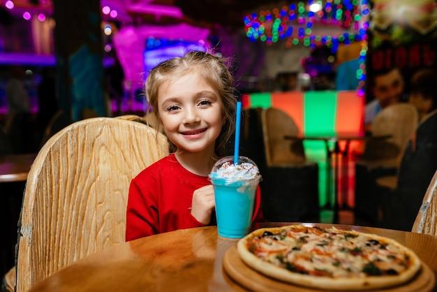 Молодая улыбающаяся девушка, одетая в красный свитер, ест мороженое в темном интерьере кафе