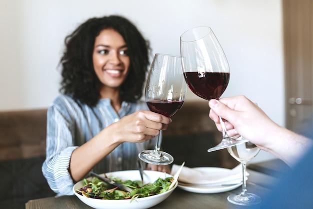카페에서 회사에서 레드 와인을 마시는 젊은 웃는 소녀. 샐러드를 먹고 레스토랑에서 와인을 마시는 꽤 아프리카 계 미국인 여자