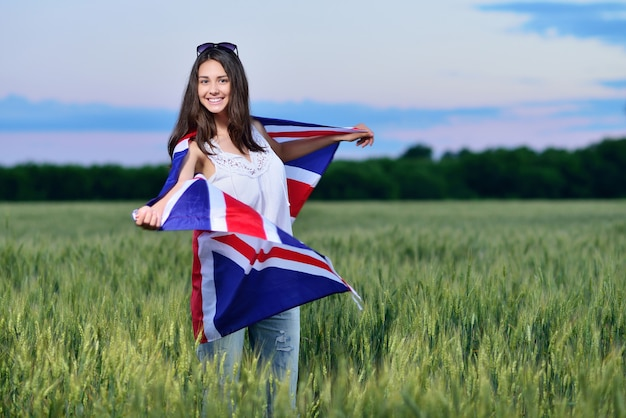 Young smiling girl in a field of wheat. flag of the great britain. the concept of learning english.