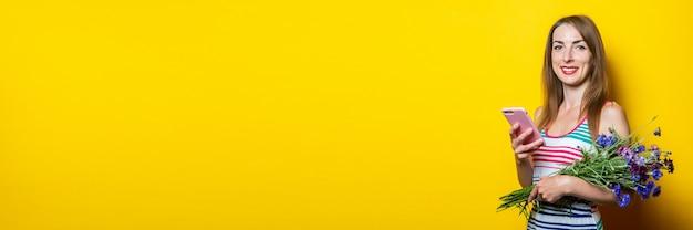 黄色の背景に携帯電話と野生の花の花束を持っている若い笑顔の女の子。バナー。