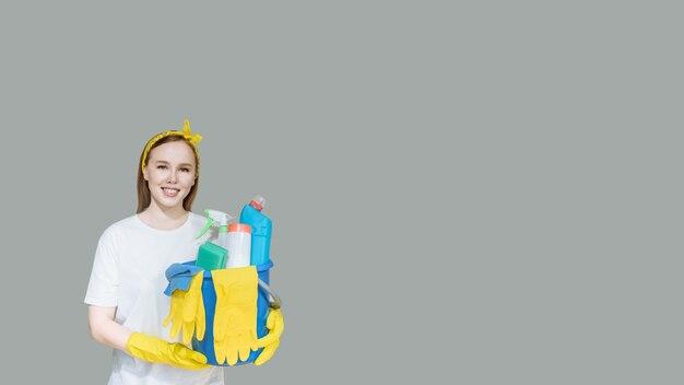 灰色の家庭用クリーニング製品と若い笑顔の女の子のメイド