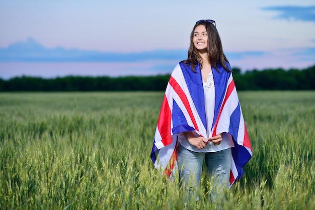 Молодая усмехаясь девушка в поле пшеницы. флаг великобритании. концепция изучения английского языка.