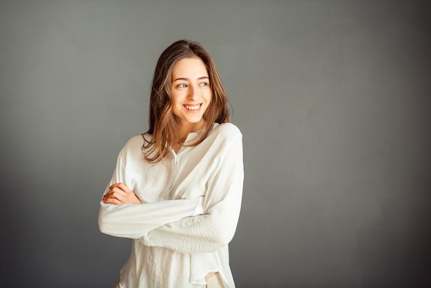 Молодая улыбающаяся девушка в белой рубашке, голова наклонена в сторону, рука у щеки, вторая в кармане, изолятор на серой стене. нет ретуши. без макияжа.