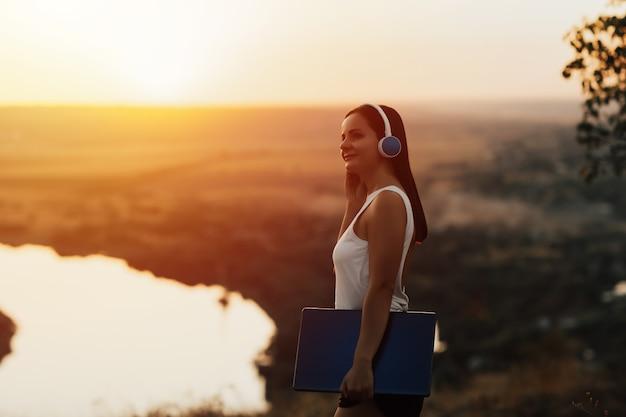 オレンジ色の夕日の丘の上に立って、音楽を聴いて、ヘッドフォンで若い笑顔の女の子。