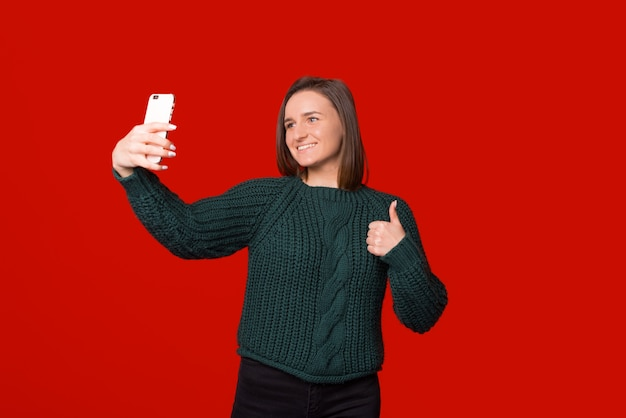 Young smiling girl is making a selfie with her phone over red background while showing thumb up.