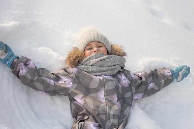 若い笑顔の女の子が遊んでいて、雪の中で横たわっています