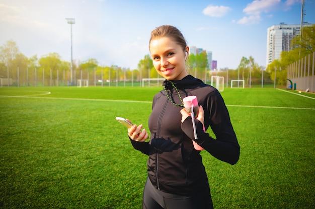 スポーツフィットネスを作り、ワイヤレスヘッドフォンで彼女の電話を使用して公園で走っている笑顔の少女