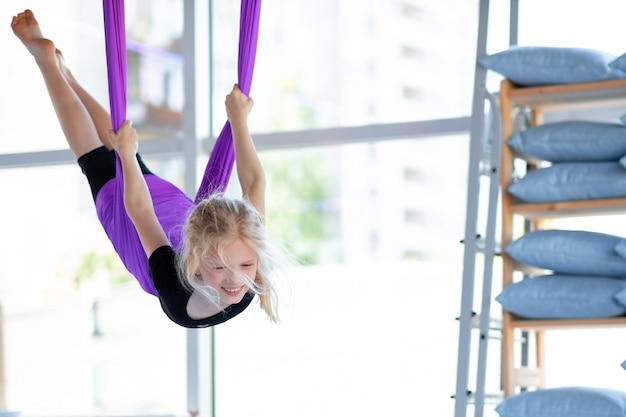 Young smiling girl practice in aero stretching swing in purple hammock in fitness club. kids aerial flying yoga exercises.