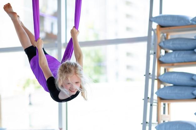 피트니스 클럽의 보라색 해먹에서 에어로 스트레칭 스윙을 하는 어린 웃는 소녀. 아이 공중 비행 요가 연습.