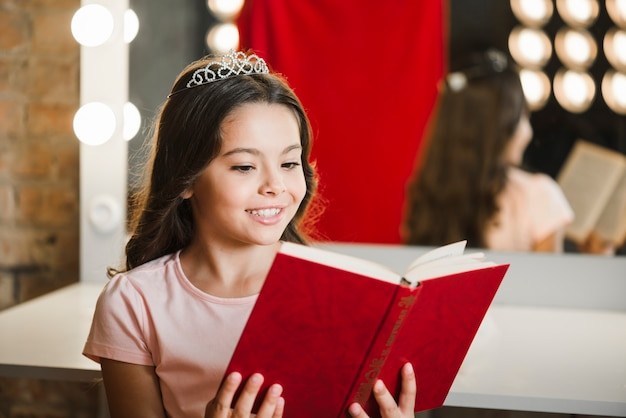 Young smiling girl reading book