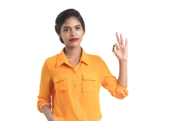 Okのサインまたは白い背景に親指を示す若い笑顔の女の子
