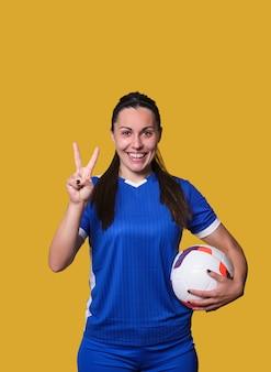 Молодая улыбающаяся девушка-футболист делает символ победы пальцами