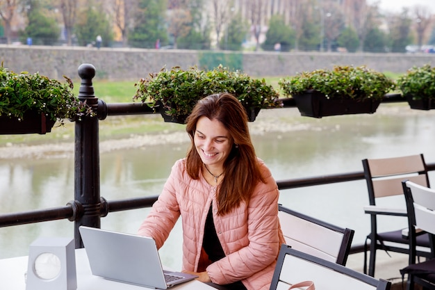 Young smiling girl using laptop for sitting at outdoor cafe, student studying using laptop