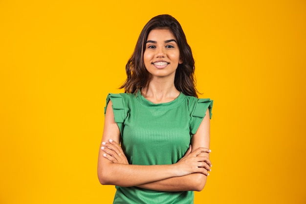Young smiling girl with arms crossed on yellow background.